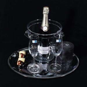 Transparante Champagnekoeler met een luxe champagne Louis Roederer. Een zilverplate serveerplateau met champagne en lekkernijen en mooie kaars.